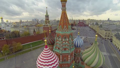 Colourful copulas of Saint Basils Cathedral against cityscape with Red square and Kremlin complex at autumn day in Moscow