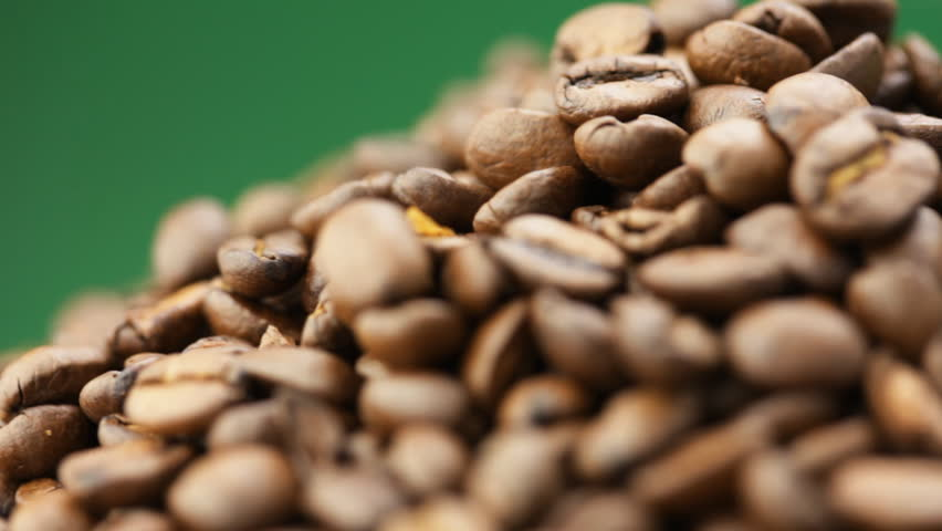 Coffee beans closeup on green  background