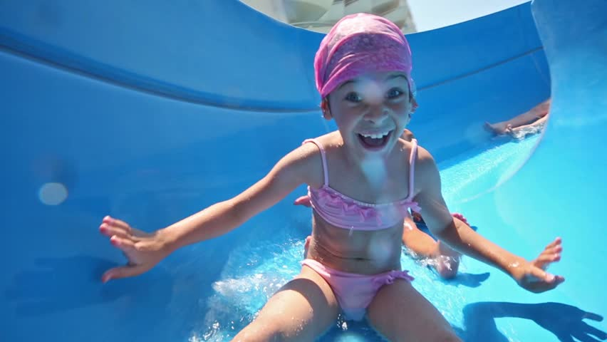 Two girls and boy rolls on blue waterslide and smiles   Shutterstock HD Video #5456354