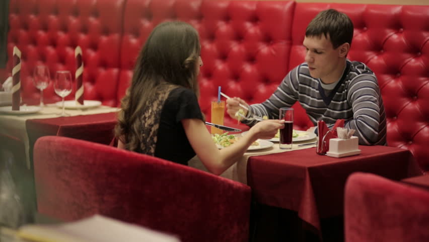 Romantic dinner in a restaurant with red leather sofas on a date