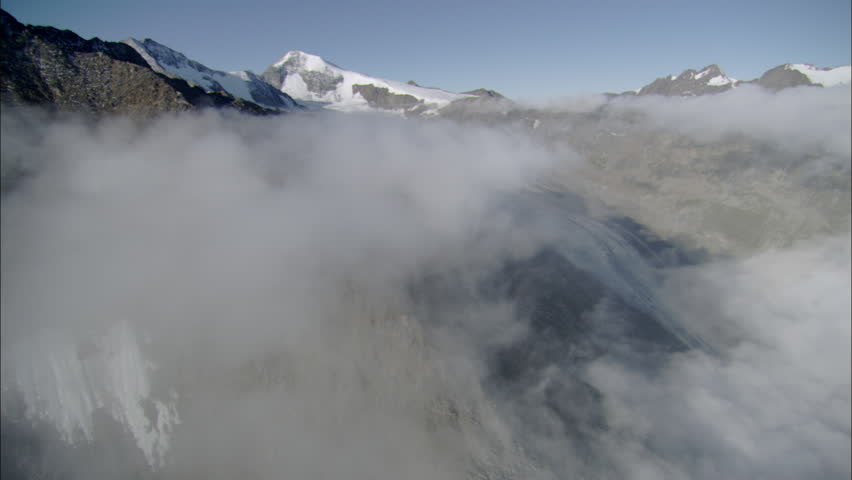 Above and in the clouds with blue sky and snowy mountains | Shutterstock HD Video #5468399