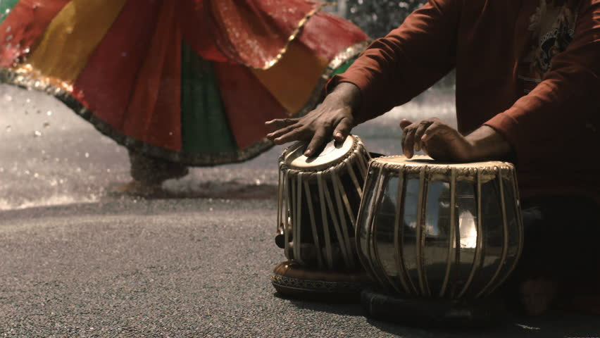 Close up of hands playing Tabla drums while feet dance in the background. Slow motion