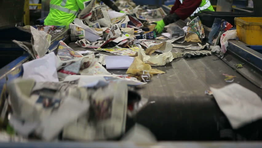FAIRFAX, VA - DECEMBER 5: Sorting paper and plastic on a conveyor belt in a recycling facility on December 5, 2013 in Fairfax, VA. The paper and plastic will be recycled.