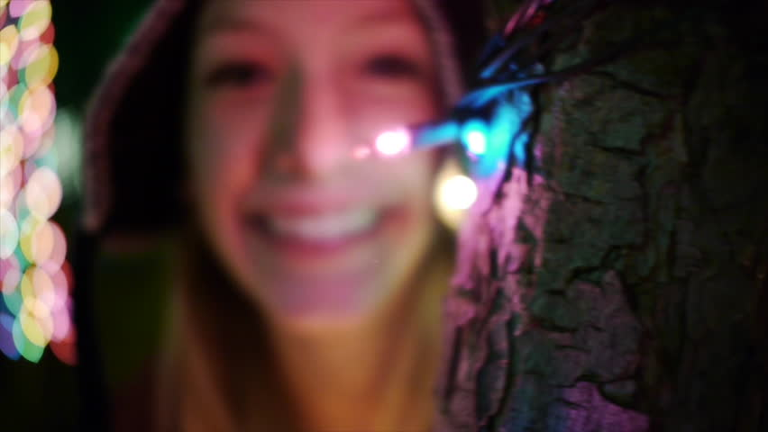Adorable Teen Girl Peers From Behind Tree Lit For The Holidays - Slo Mo Close Up