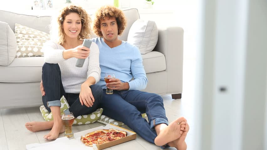 Cheerful couple at home having pizza in font of TV