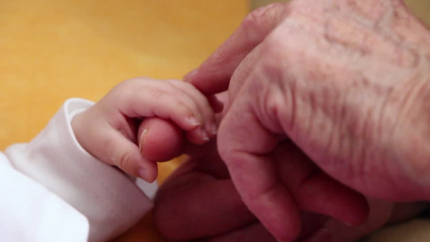 Hand in hand. Grandmother holds the hand of a newborn