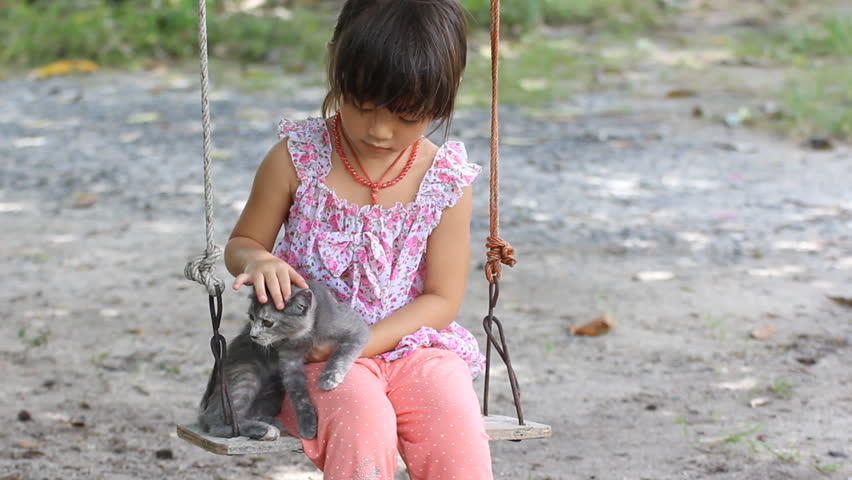 good cat and little girl sit on a swing