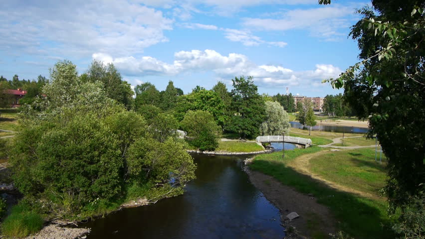 Beautiful view of public garden with narrow river and small bridge across in Petrozavosk, Russia