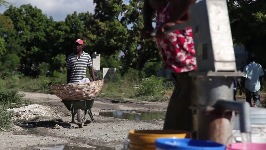 PORT AU PRINCE, HAITI - DECEMBER 17, 2013: Unidentified woman pumping water at well and unidentified man passing with wheelbarrow in the outskirts of Port au Prince, Haiti.