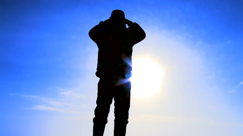 Silhouette of man standing and enjoying the view in front of blue sky on sunny day.