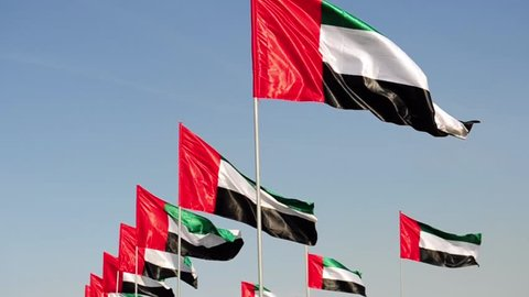 Flags of UAE waiving on the wind in day time.