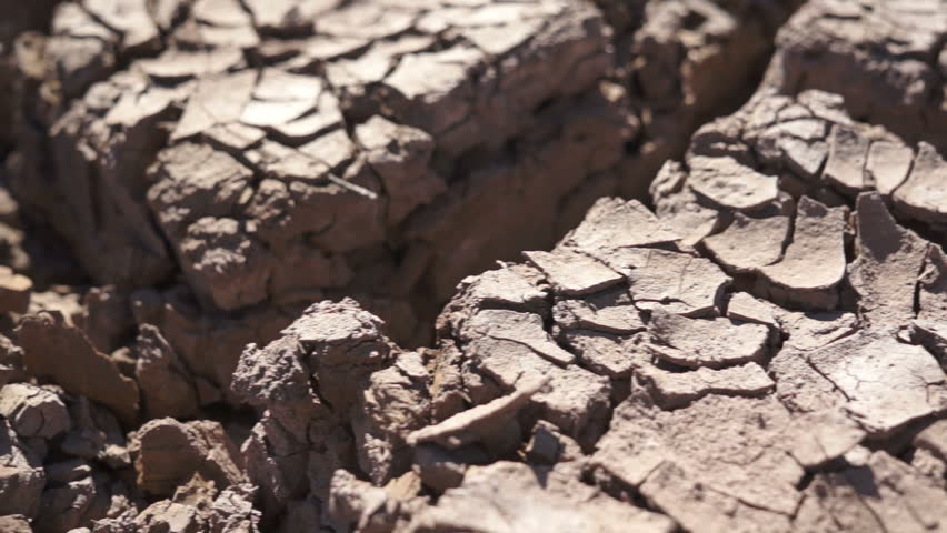 Extreme close up dolly shot of dried and cracked earth caused by lack of rain and hot sun and producing a drought.