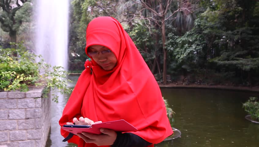HONG KONG, SAR CHINA - JANUARY 12:   Traditionally dressed Indonesian woman checks her mobile tablet cell phone in Kowloon park on Sunday afternoon, January 12, 2014.
