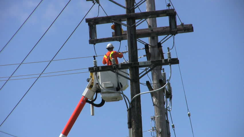 A hydro repair man in an orange jumpsuit and hard hat repairs a problem on the line.