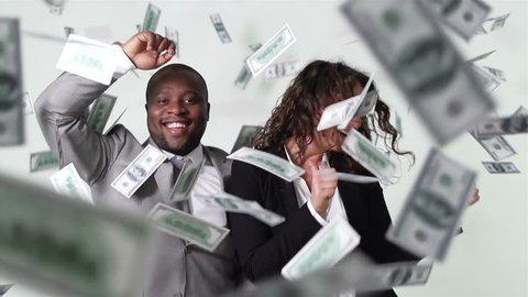 Business partners having fun dancing among flying cash in slow motion