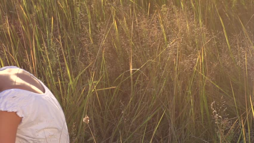 Beauty Girl with Healthy Long Hair Outdoors. Happy Smiling Young Woman falling down on the grass. Beautiful young woman lying on the field. Enjoying Nature. Slow motion video footage. Slowmo 240 fps
