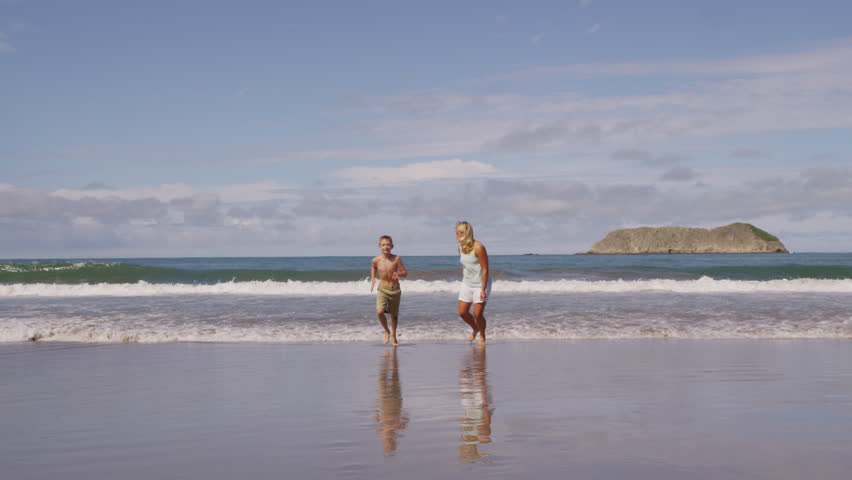 Mother and son running at beach slow motion. Shot on RED EPIC for high quality 4K, UHD, Ultra HD resolution.   Shutterstock HD Video #5584841