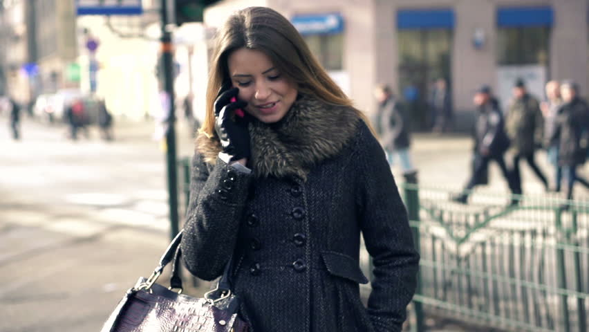 Young attractive woman talking on mobile phone in the city, slow motion