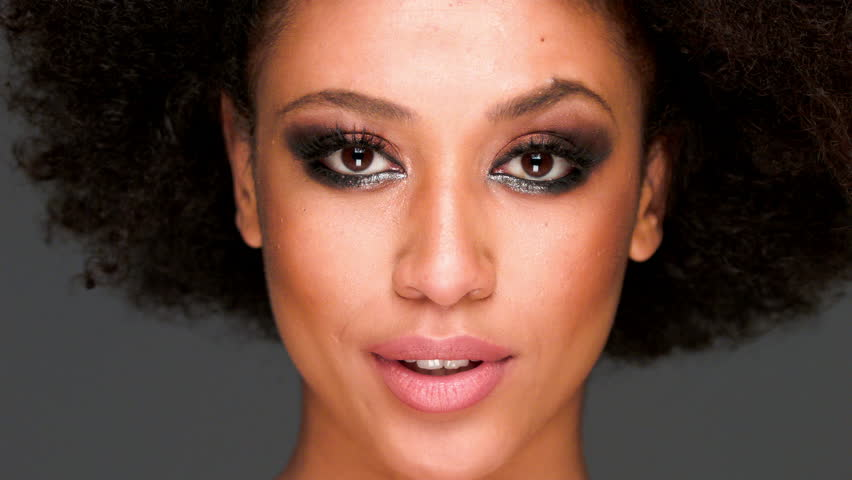 Beautiful sexy sensual young African American woman biting her lip close up of her face on grey