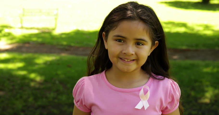 Smiling little girl wearing pink for breast cancer awareness in the park on a sunny day