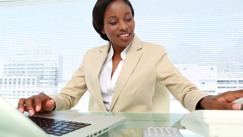 African-american Businesswoman talking on phone and using laptop at desk in her office