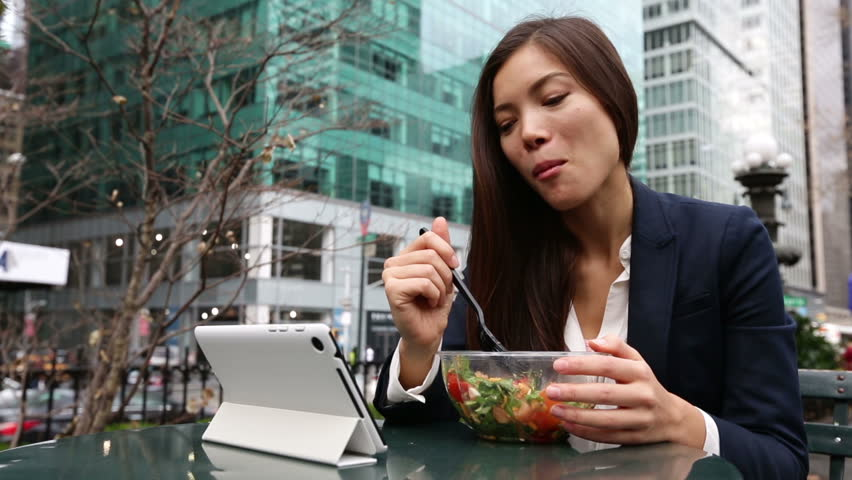 Business woman using tablet computer pc eating salad on lunch break in City Park living healthy lifestyle. Happy smiling mixed Asian young businesswoman, Bryant Park, Manhattan, New York City, USA | Shutterstock HD Video #5658221