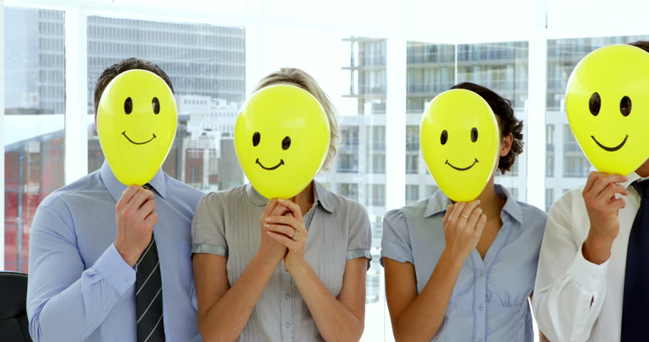 Business team holding smiley face balloons in the office