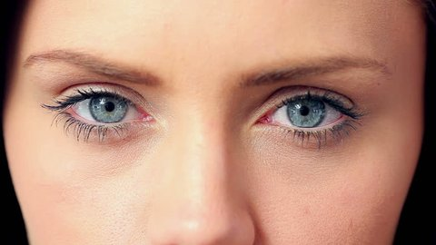 Brunette opening her blue eyes in extreme close up