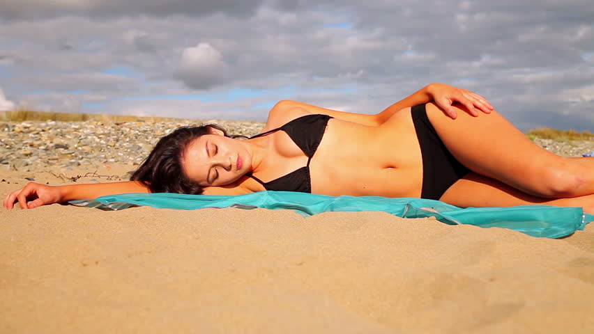 Gorgeous brunette lying on the beach on a scarf on a cloudy day
