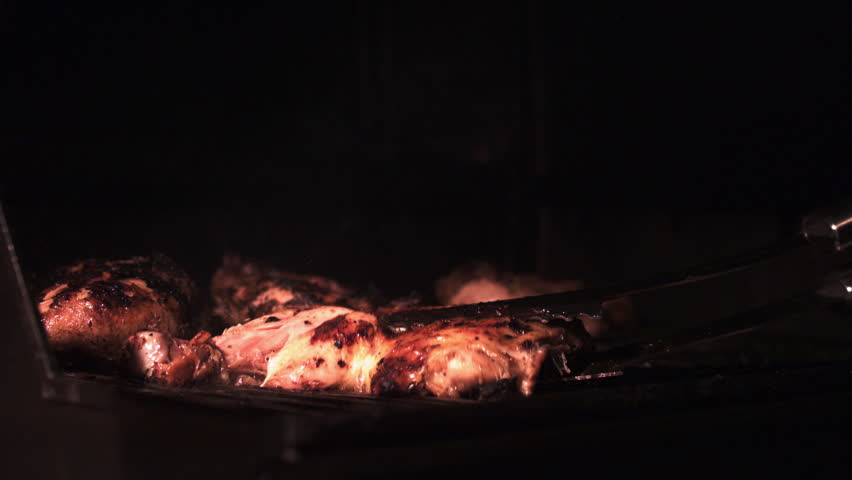 Grilling Barbecue Chicken. Slow Motion 1000fps. Fiery Grill Top Flaming As Chicken Is Being Cooked. Chicken Thrown On Grill (Shot On Phantom)