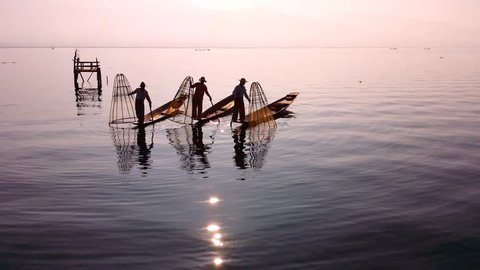 Myanmar, Burma Inle Lake fishermen fishing on traditional boat at sunset. Beautiful reflection of evening sun and silhouettes in water. Famous tourist travel destination 4k ultra high definition video