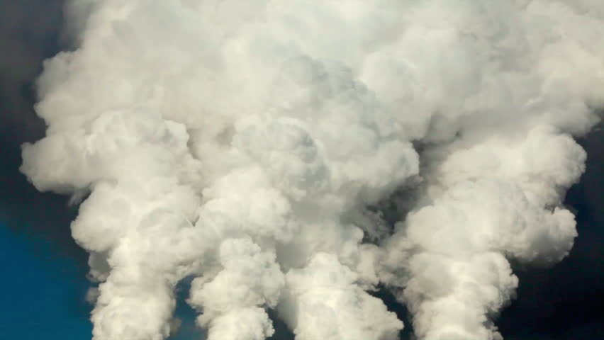 Dramatic view of of four smoke or steam columns with total clouds above. Dioxide carbon and warm, exhausting with the industry chimneys in the atmosphere, is the great danger for global ecology.