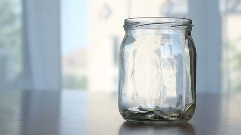 Savings in the jar, coins falling into the jar
