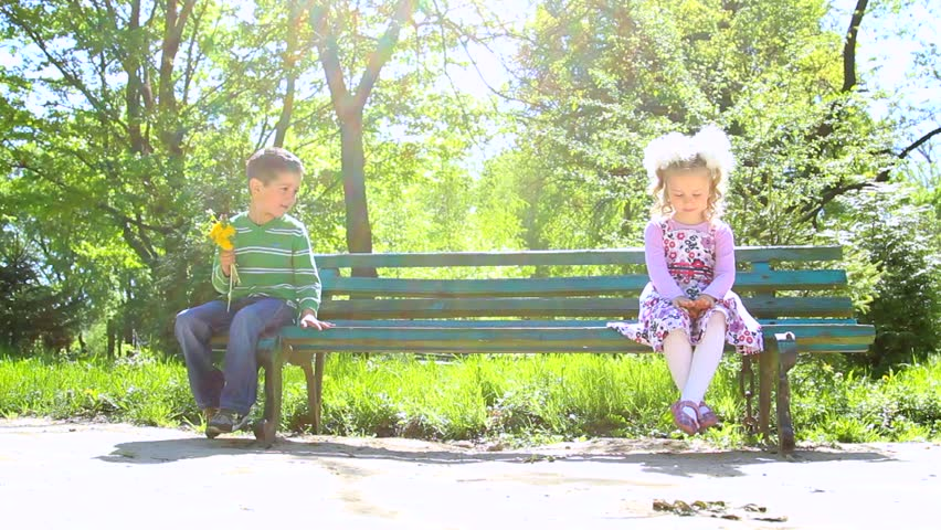 Delightful Video Bench Part - 3: Children Sitting On Bench In Green Sunny Park. Boy With Fields Flowers In  Hand Is
