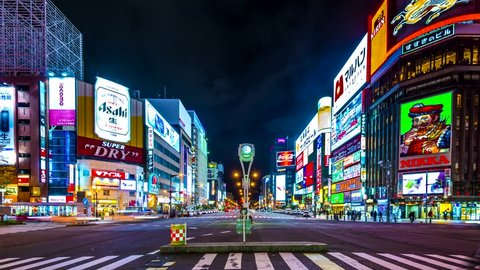 SAPPORO, JAPAN - OCTOBER 23, 2013: Pedestrians and traffic pass through Susukino district at night. Susukino is designated one of the three major red-light districts of Japan.