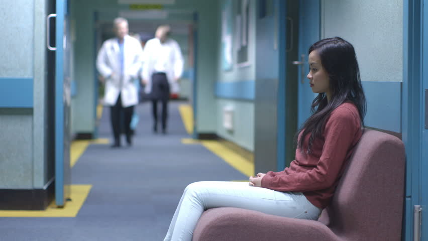 Worried young woman sitting alone in a hospital waiting area waits for news.