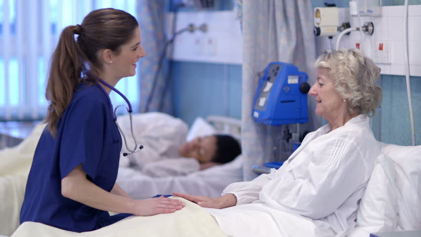 Caring nurse chats with an elderly female patient on a hospital ward. #5784101