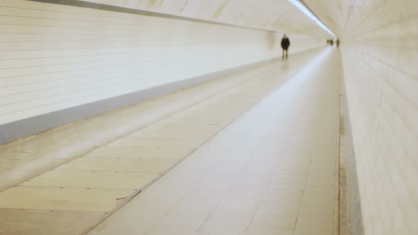 Shallow depth of field shot of an unrecognizable middle aged man walking alone with his hands in his pocket, far from a group in a long circular round concrete pipe shaped tunnel.