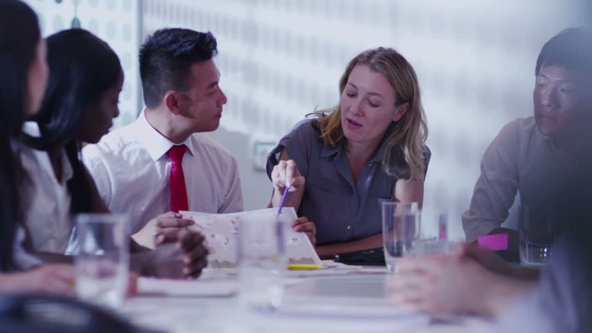 Cheerful mixed ethnicity business team brainstorming in a boardroom meeting.   Shutterstock HD Video #5843801