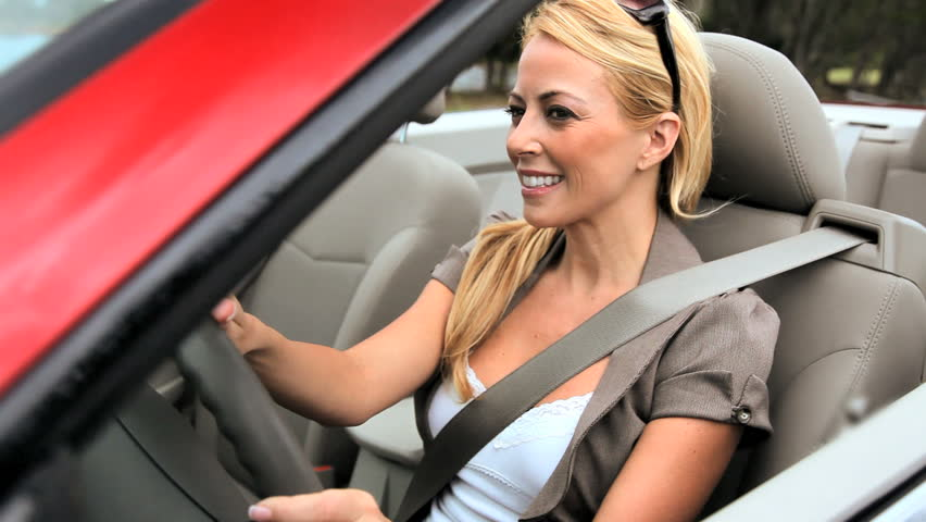 Successful young businesswoman enjoying the sunshine while driving her luxury open top car