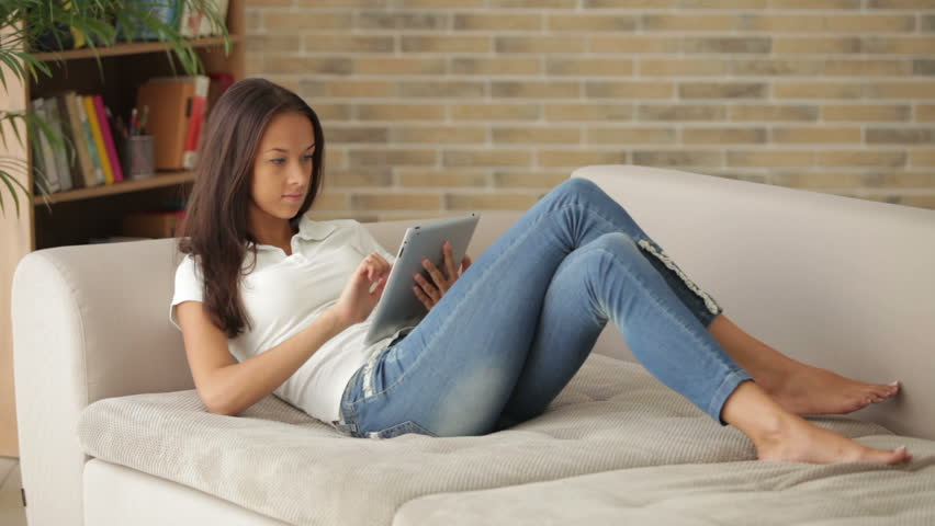 Hy Relaxing On Couch Using Touchpad Looking At Camera And Smiling