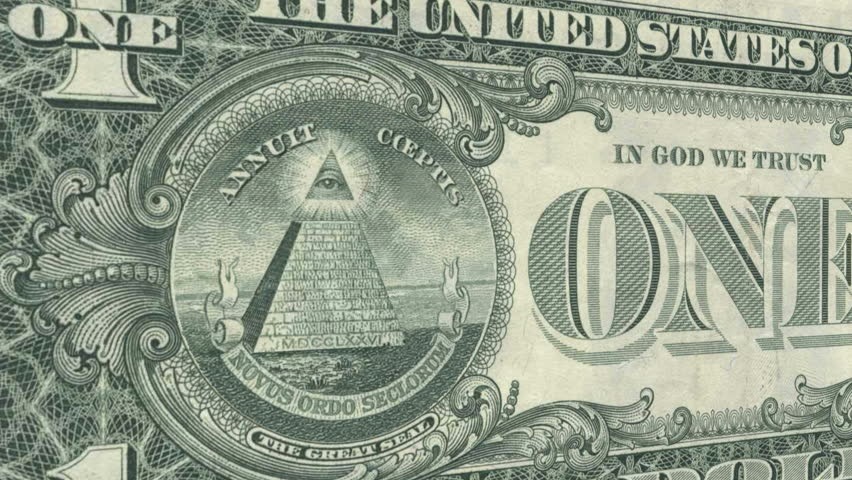 The All Seeing Eye on the back of the US Dollar Bill glows and emits rays of light as the camera draws closer.