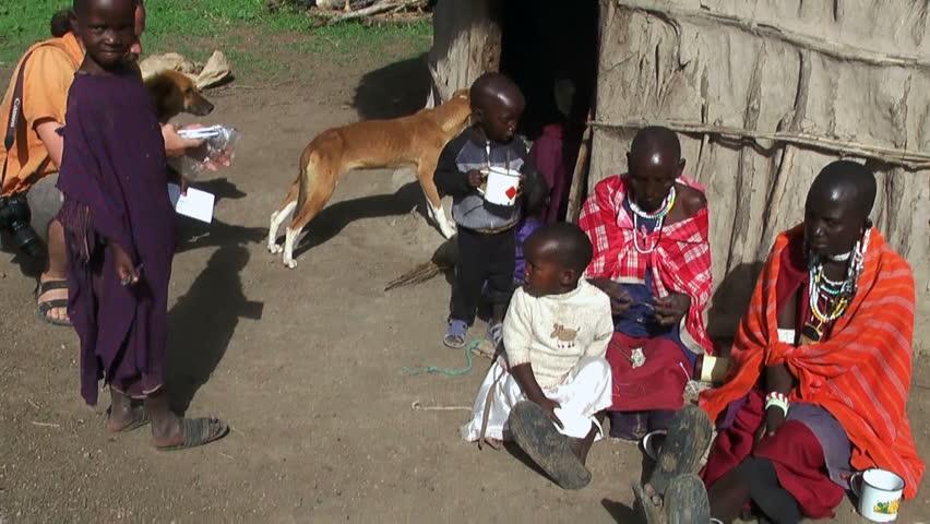 ARUSHA, TANZANIA - CIRCA DECEMBER, 2011: Masai children with parents are in big Tanzanian family. Visiting Tanzanian masai village during Africa expedition   Shutterstock HD Video #5871371