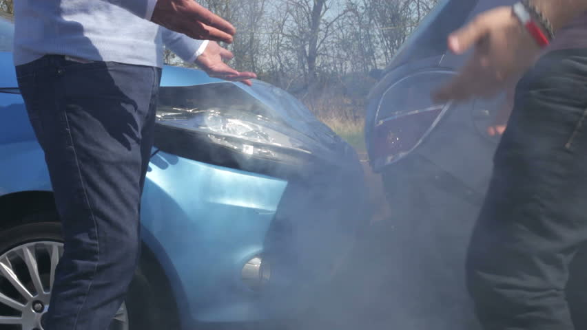 Two drivers argue about blame for accident by the side of damaged and smoking vehicles - camera pans from feet to faces.Shot on Canon 5d Mk2 with a frame rate of 30fps