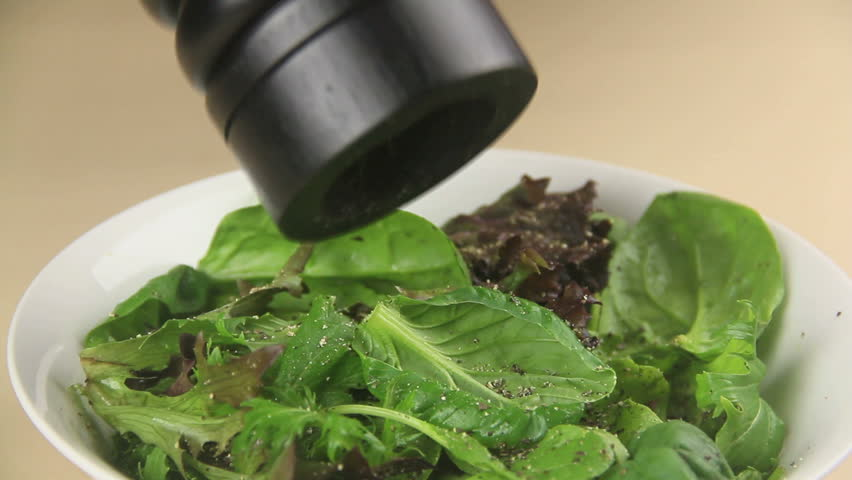 Close up of a pepper mill grinding pepper on to a garden salad.