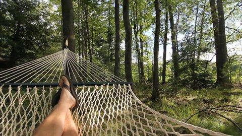 Summer Hammock. POV shot of man relaxing in a hammock. Muskoka, Ontario, Canada.