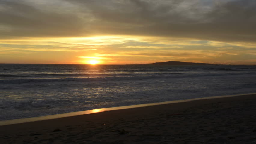 A beautiful sunset in Huntington Beach, California shows distend land and small waves reflecting the sunlight.