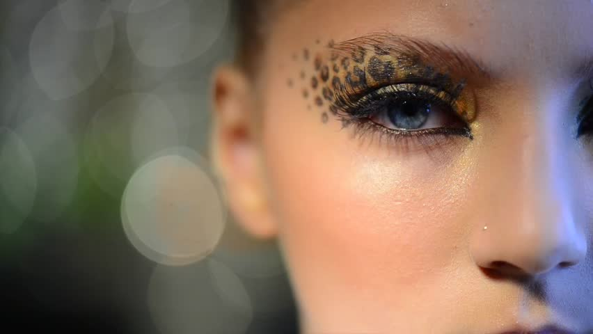 Party Makeup. Beauty Fashion Model Girl with Holiday Leopard Make up. Golden Wild Cat Eyes Make-up Eyeshadow. Beautiful Woman Face over Blinking Background.