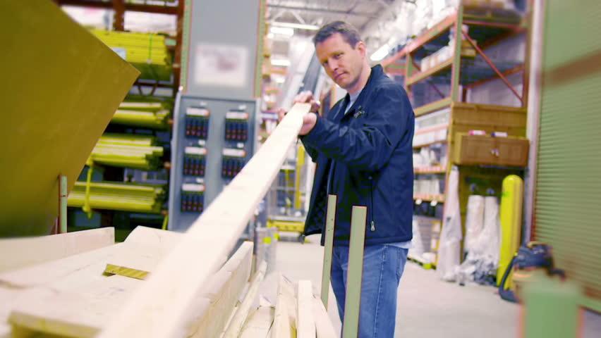 A man picks out lumber at a big box hardware store.