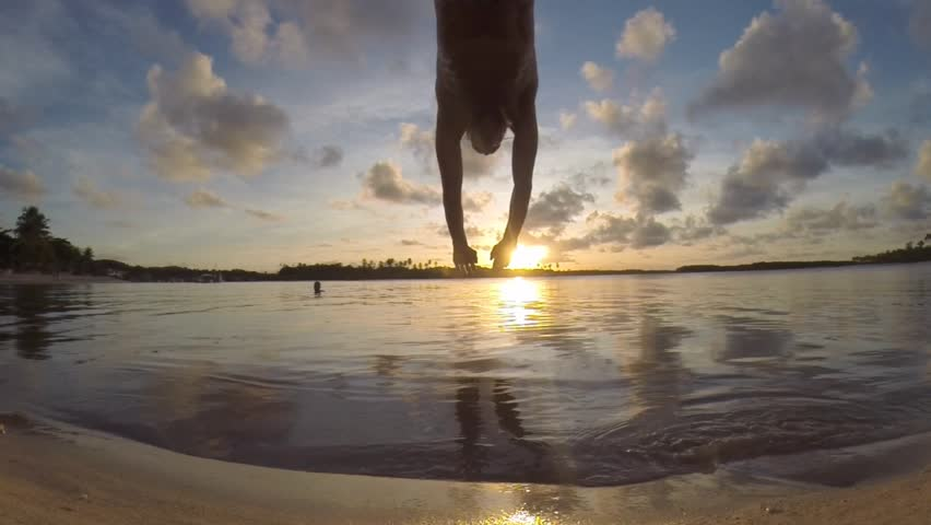 Man diving slow motion into smooth water with sunset reflection ripples